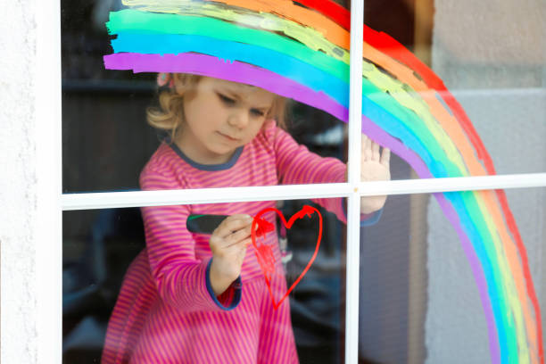 Adoralbe little toddler girl with rainbow painted with colorful window color during pandemic coronavirus quarantine. Child painting rainbows around the world with the words Let's all be well. stock photo