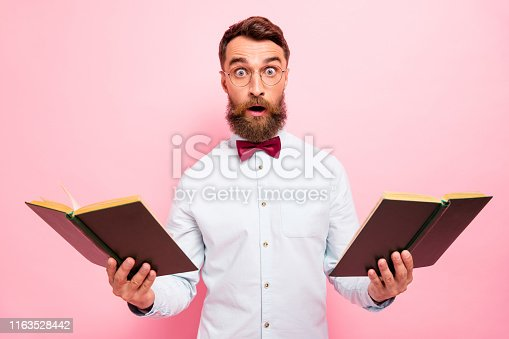 istock I adore history concept. Photo of mad loony scientist holding two opened books in hands wearing white shirt isolated pastel background 1163528442