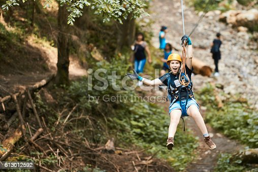 happy woman on tyrolean traverse enjoying adventure, looking at camera with arms raised and feeling free.