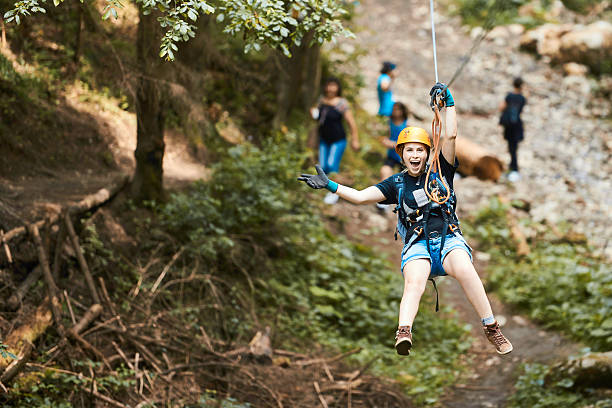 adrenaline and freedom happy woman on tyrolean traverse enjoying adventure, looking at camera with arms raised and feeling free. zip line stock pictures, royalty-free photos & images