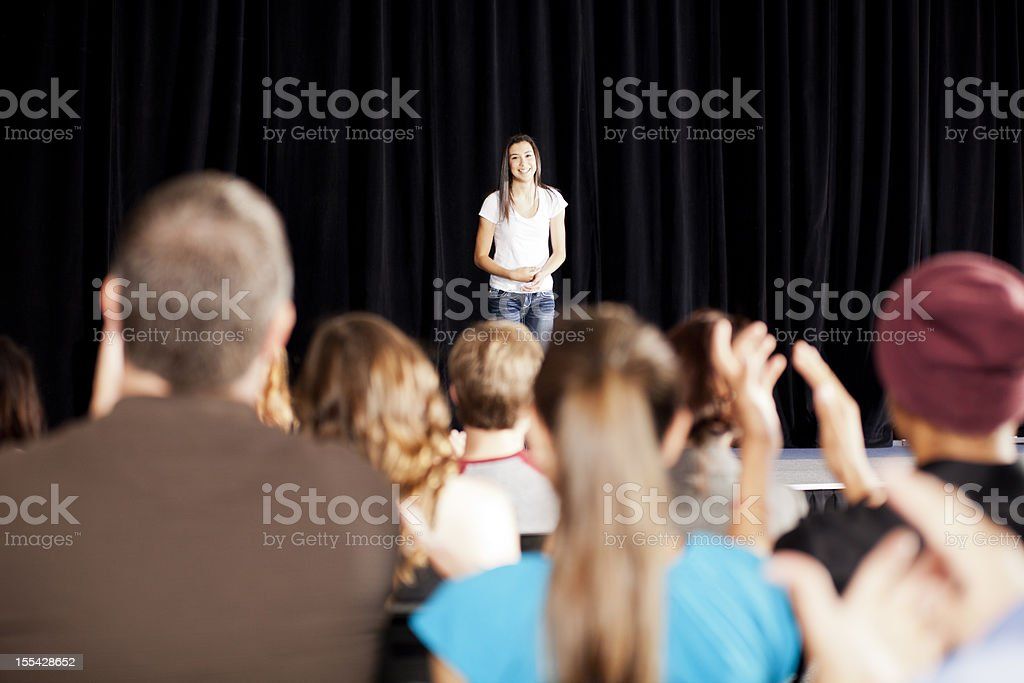 Adudience clapping for a teenage girl on stage stock photo