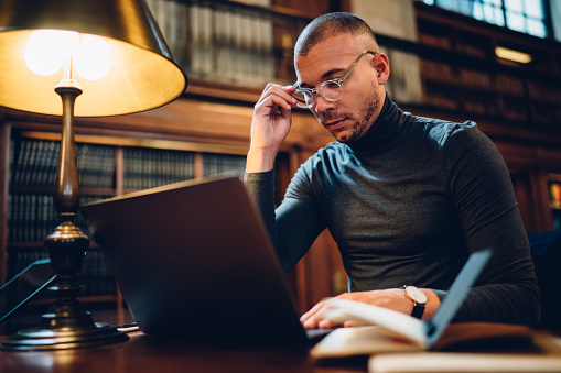 istock Adult 30 years old male student spending time in university library library for learning, intelligent man in optical spectacles searching for scientific information via modern laptop computer 1158476121