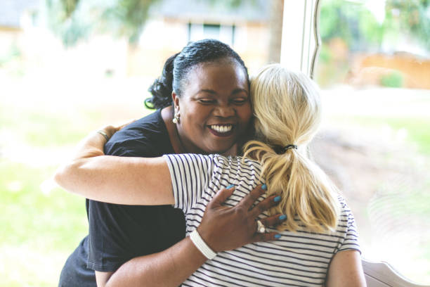 adult african american female and caucasian at front door of residence greeting each other with an embrace - vizinho imagens e fotografias de stock