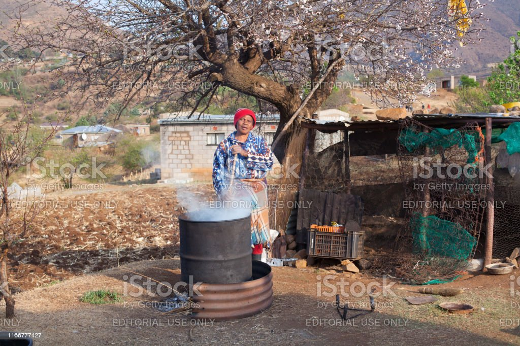 adult african woman in traditional blanket dress brews national drink...