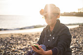 Adult aged caucasian woman looking and writing on the hone at the beach during outdoor leisure activity - ocean and sunset with sun backlight - casual with hat - technology and vacation concept