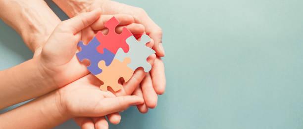 erwachsene und chiild hände halten puzzle-form, autismus-bewusstsein, autismus-spektrum-familie unterstützung konzept, welt-autismus-bewusstsein-tag - autismus stock-fotos und bilder