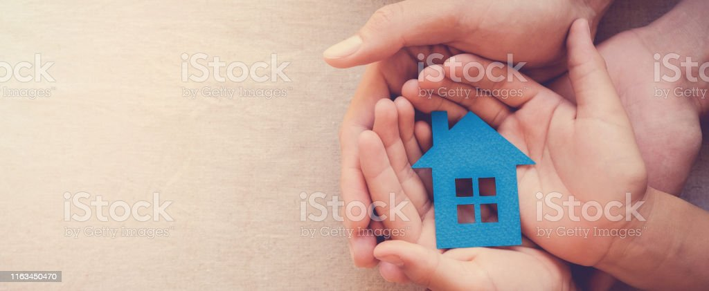Adult and child hands holding blue paper house for family home and homeless shelter concept - Foto stock royalty-free di Adulto