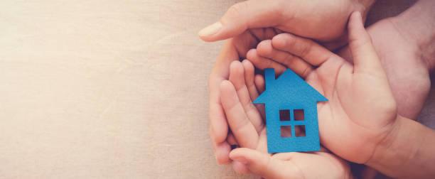 mani per adulti e bambini che tengono la casa di carta blu per la casa di famiglia e il concetto di rifugio per senzatetto - protezione foto e immagini stock