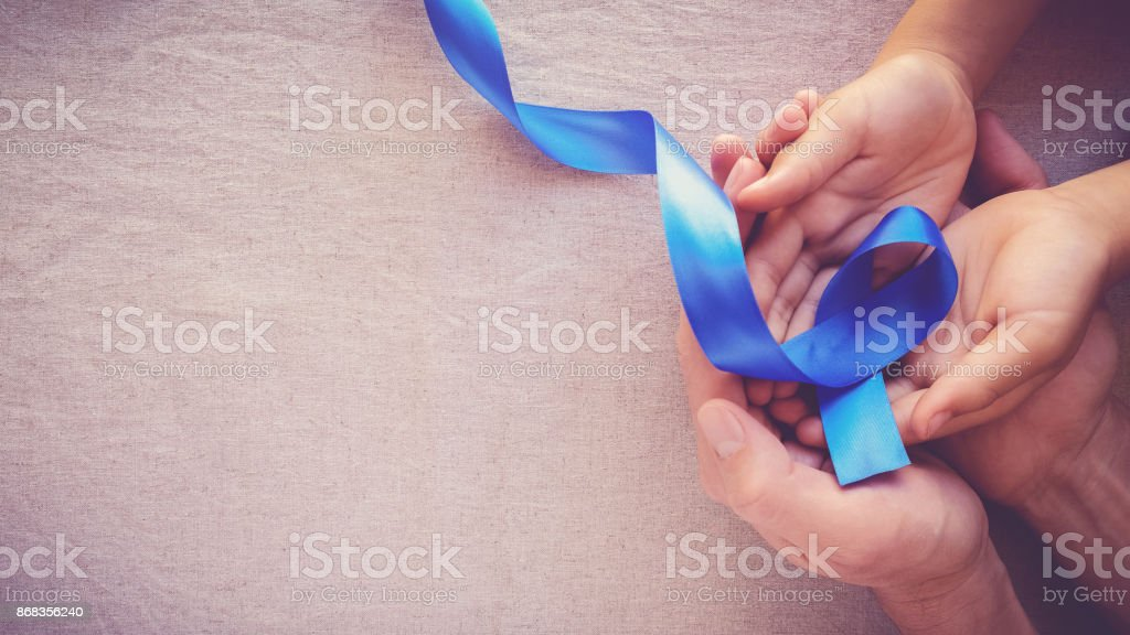 adult and child hands holding Blue ribbon, Colon Cancer, Colorectal Cancer, Child Abuse awareness, world diabetes day stock photo