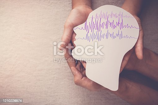 Adult and child hands holding encephalography brain paper cutout, Epilepsy awareness, seizure disorder, mental health concept