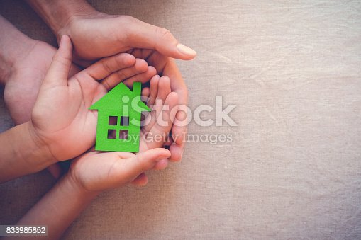istock Adult and child hands holding green paper house, eco house concept 833985852
