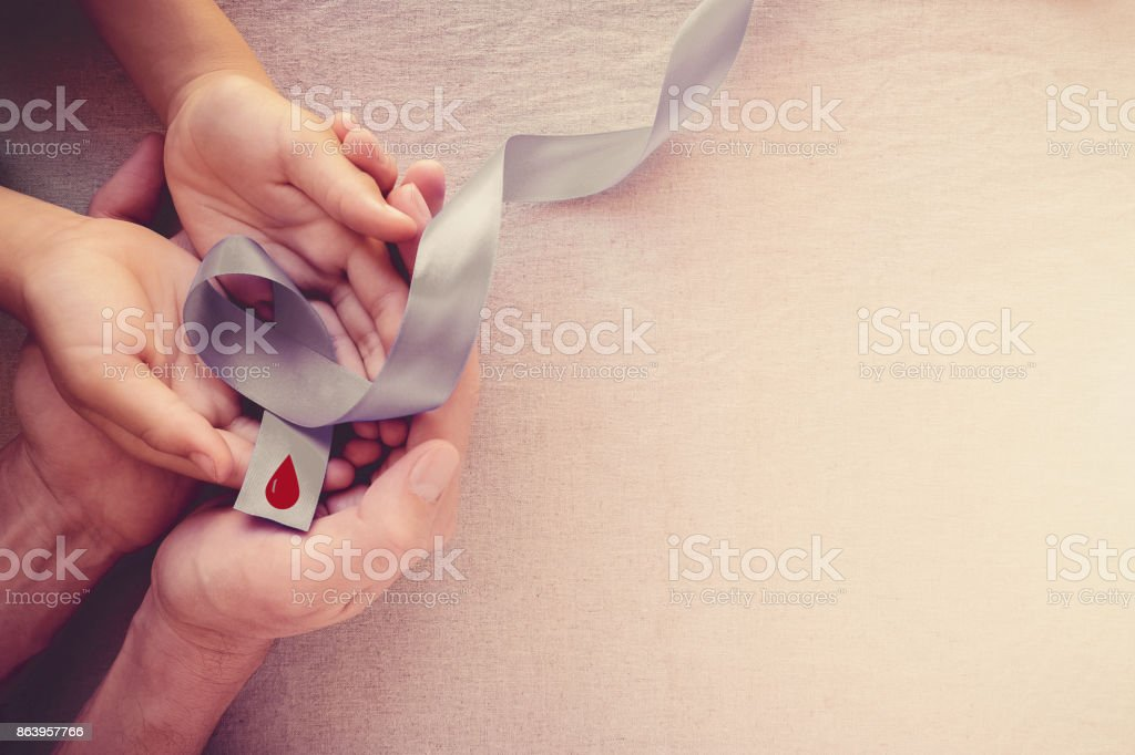 Adult and child hands holding grey ribbon, World Diabetes day stock photo