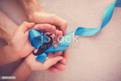 istock Adult and child hands holding Light blue ribbons with mustache , Prostate Cancer Awareness, Men health awareness, Movember month 868356038