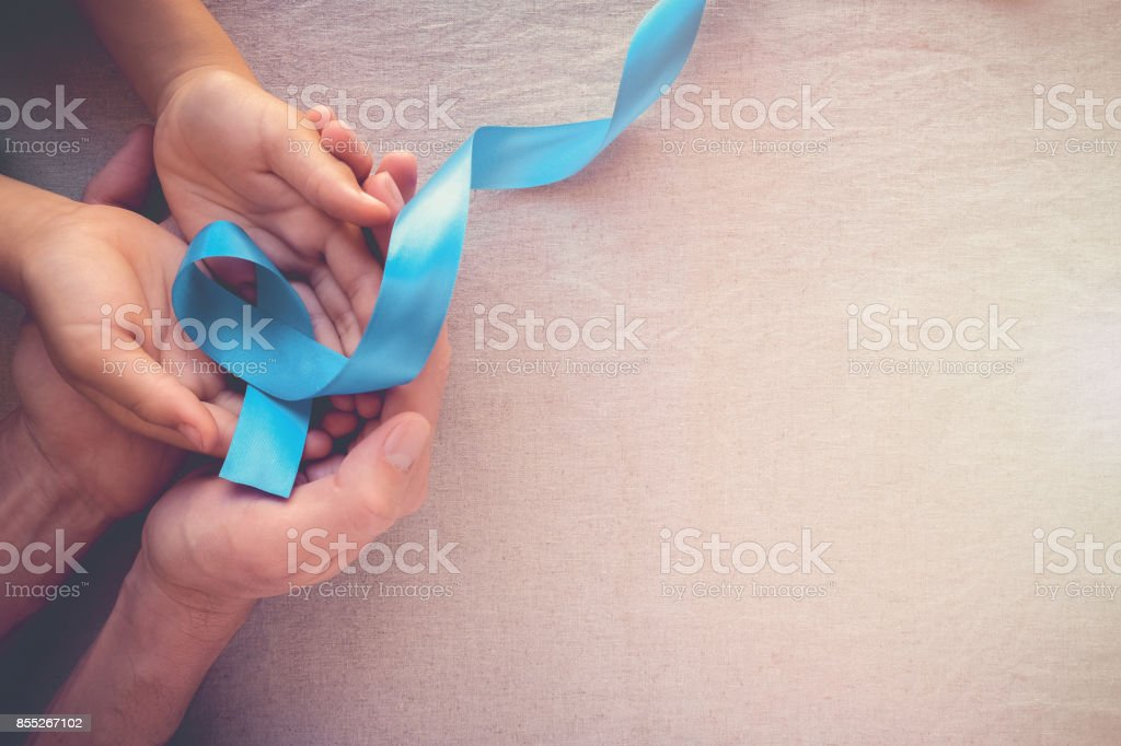 Adult and child hands holding Light blue, sky blue ribbons, toning background, Prostate Cancer Awareness and Adrenocortical carcinoma awareness stock photo