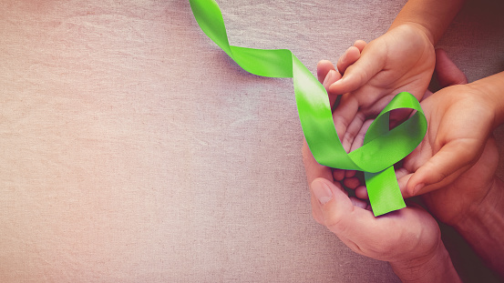 Adult And Child Hands Holding Lime Green Ribbon Panoramic ...