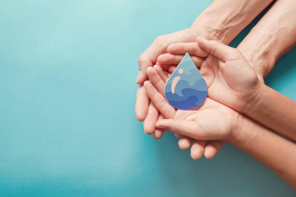 Erwachsene und Kinder Hände halten Papier geschnitten Wassertropfen, Weltwassertag, sauberes Wasser und sanitäre Einrichtungen, CSR, Wasser sparen, Ökologie-Konzept – Foto