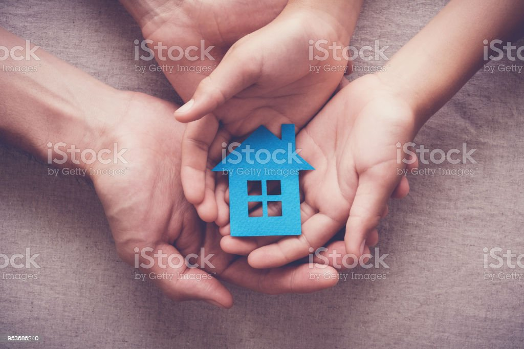 Adult and child hands holding paper house, family home and homeless shelter concept stock photo