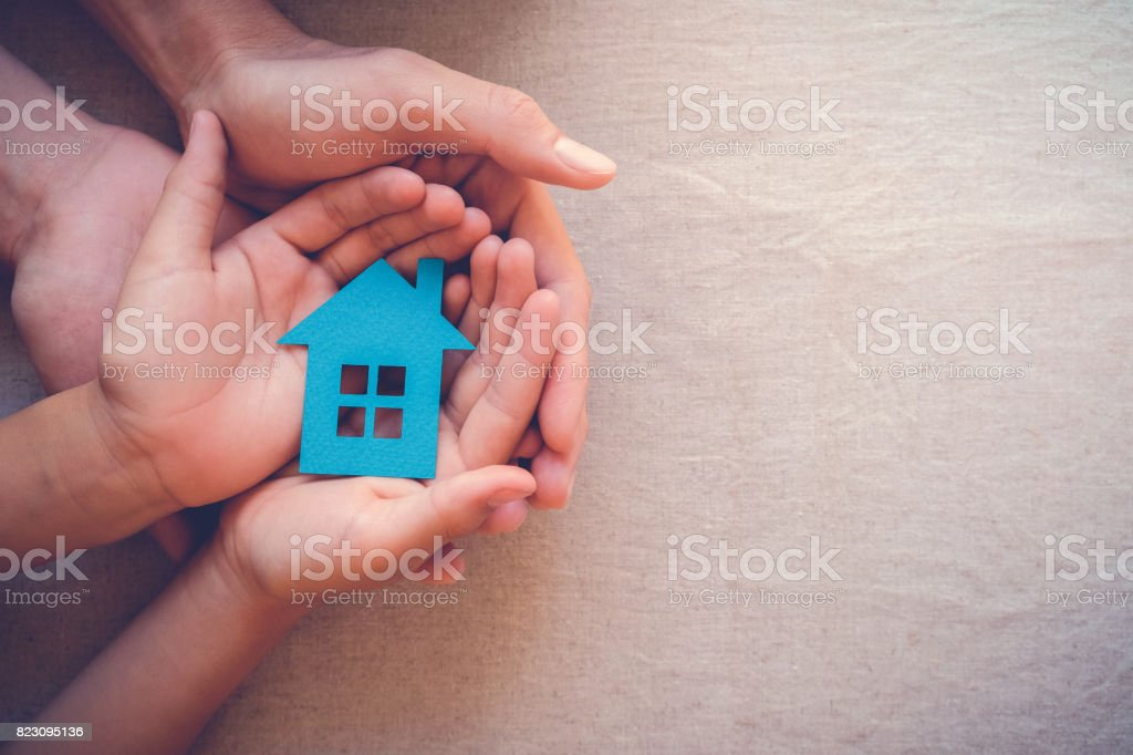 Adult and child hands holding paper house, family home and real estate concept royalty-free stock photo