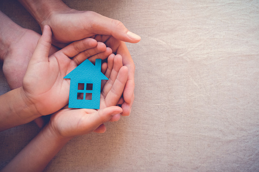 istock Adult and child hands holding paper house, family home and real estate concept 823095136