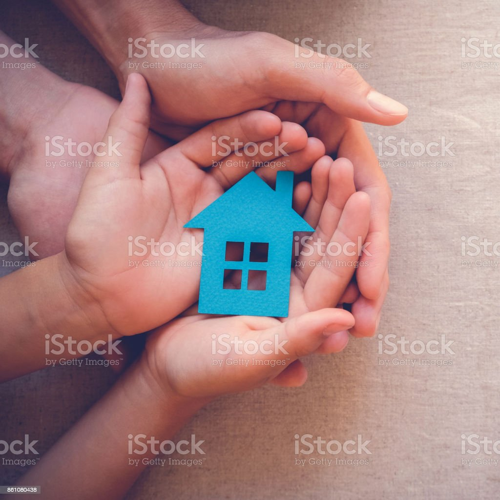 Adult and child hands holding paper house, family home and real estate concept stock photo