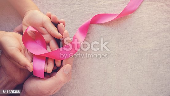istock Adult and child hands holding pink ribbons, Breast cancer awareness, abdominal cancer awareness and October Pink panoramic background 841425366