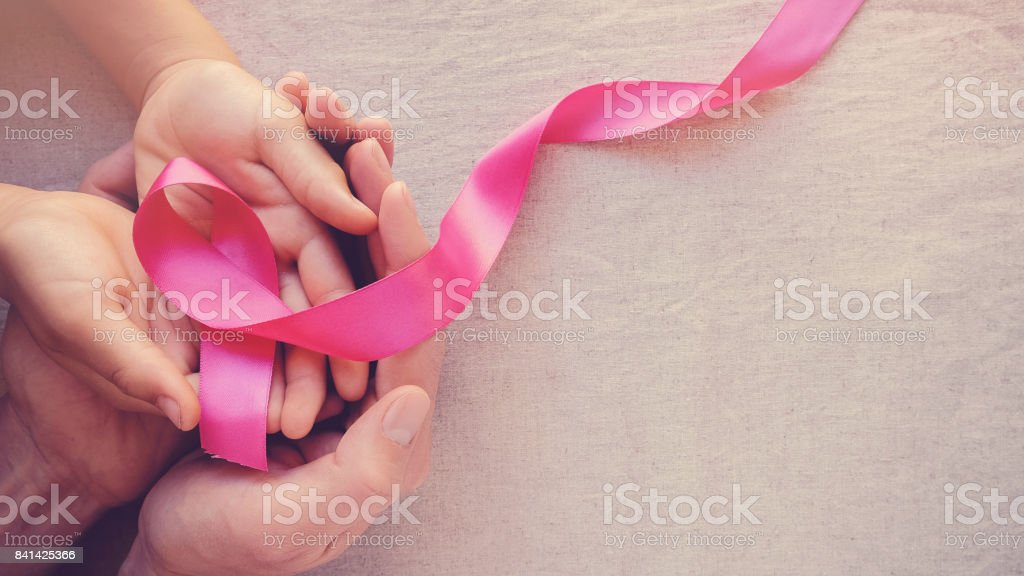 Adult and child hands holding pink ribbons, Breast cancer awareness, abdominal cancer awareness and October Pink panoramic background stock photo