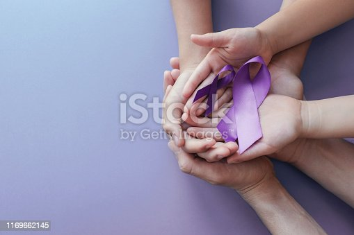 istock Adult and child hands holding purple ribbons, Alzheimer's disease, Pancreatic cancer, Epilepsy awareness, world cancer day on purple background 1169662145
