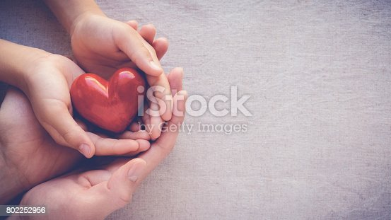istock adult and child hands holding red heart, health care love and family concept 802252956