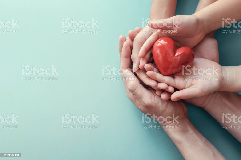 adult and child hands holding red heart on aqua background, heart health, donation, CSR concept, world heart day, world health day, family day - Стоковые фото World Blood Donor Day роялти-фри