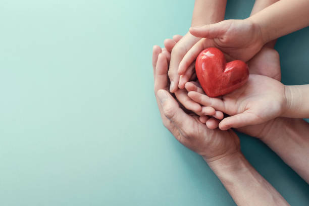 adult and child hands holding red heart on aqua background, heart health, donation, CSR concept, world heart day, world health day, family day adult and child hands holding red heart on aqua background, heart health, donation, CSR concept, world heart day, world health day, family day healthcare and medicine stock pictures, royalty-free photos & images