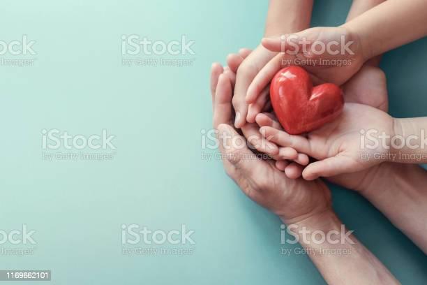 Adult And Child Hands Holding Red Heart On Aqua Background Heart Health Donation Csr Concept World Heart Day World Health Day Family Day - Fotografias de stock e mais imagens de Acolhimento familiar