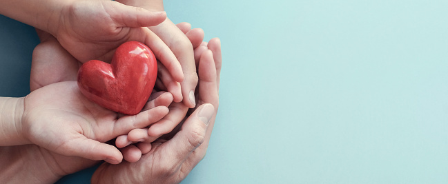 istock adult and child hands holding red heart on aqua background, heart health, donation, CSR concept, world heart day, world health day, family day 1173492442