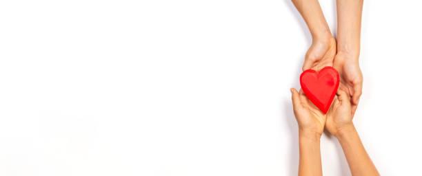 Erwachsene und Kind Hände halten rotes Herz über weißem Hintergrund. Liebe, Gesundheit, Familie, Versicherung, Spendenkonzept – Foto