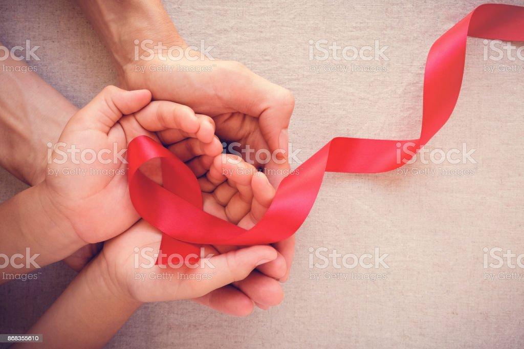 adult and child hands holding red ribbon, hiv awareness concept, world AIDS day stock photo