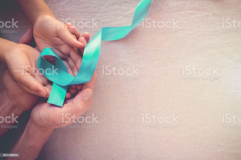 Adult and child hands holding Teal Ribbon, toning background, Ovarian Cancer, cervical Cancer, Kidney Cancer and sexual assault awareness stock photo
