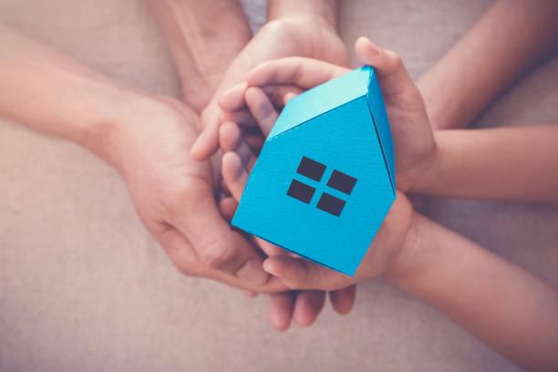 Erwachsenen- und Kinderhände mit Weißem Haus, Familienhaus und Obdachlosenheim-Konzept – Foto