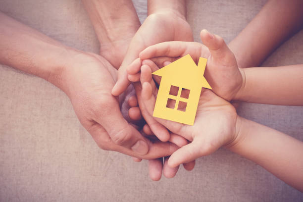 Adult and child hands holding yellow house, family home and homeless shelter concept stock photo