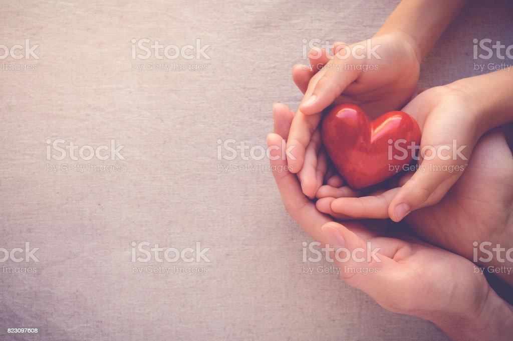 adulte et enfant mains vinifie rouge au cœur, l'amour de la santé et notion de famille photo libre de droits