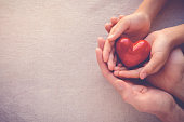 istock adult and child hands holiding red heart, health care love and family concept 823097608