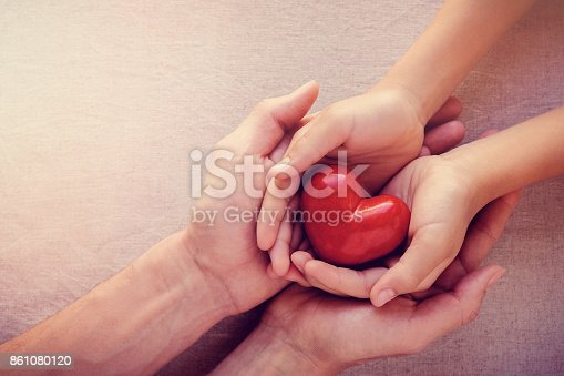 istock adult and child hands holiding red heart, health care love, give, hope and family concept 861080120