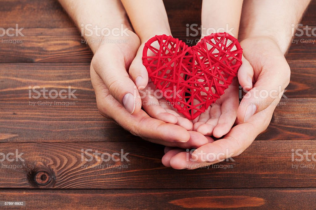 Adult and child holding red heart, family relationships, health care stock photo