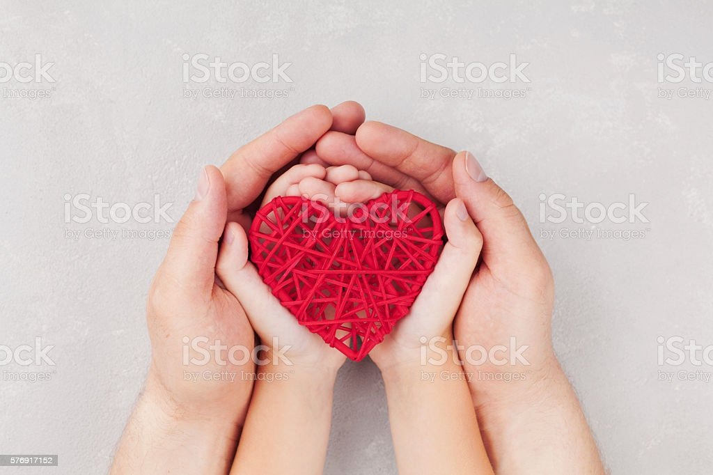 Adult and child holding red heart in hands. Family. Cardiology. – Foto