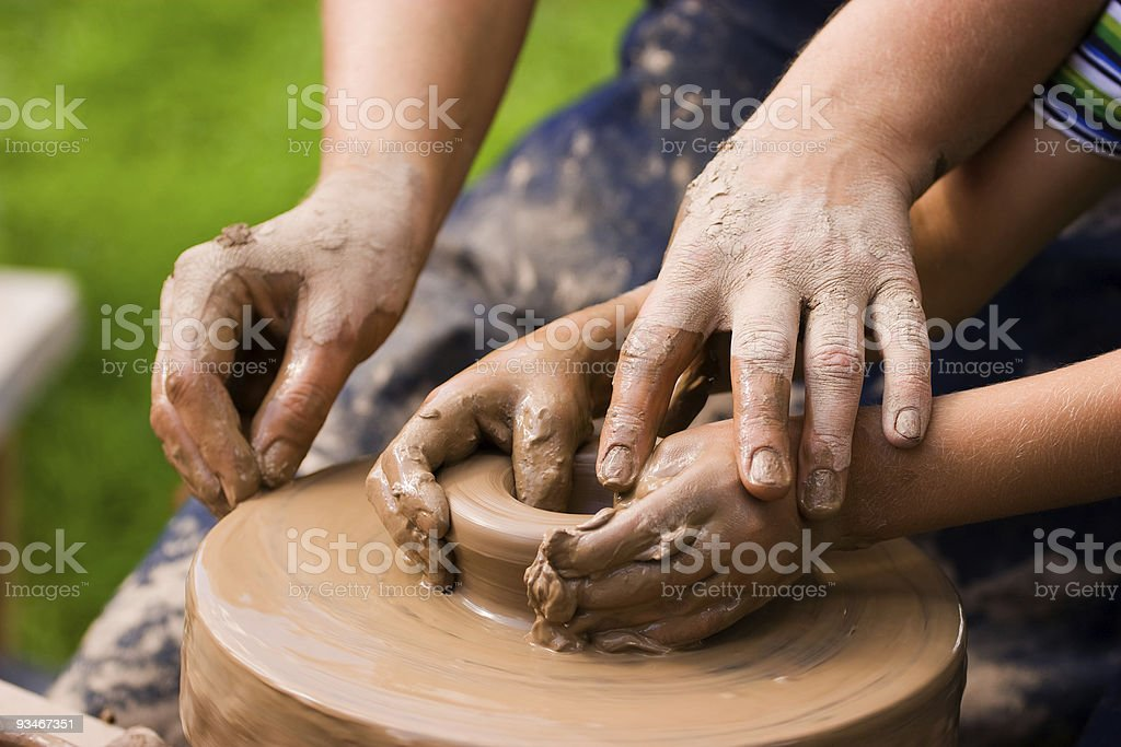 Adult and child working as a potters team stock photo