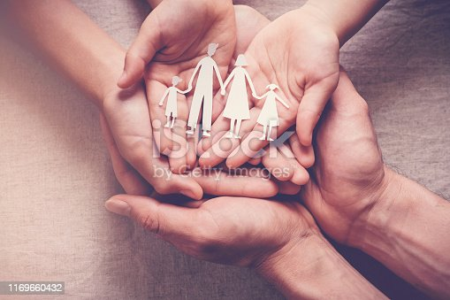 Adult and children hands holding paper family cutout, family home, foster care, homeless charity support concept