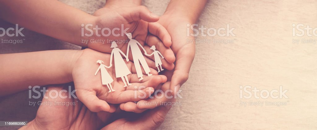 Adult and children hands holding paper family cutout, family home, foster care, homeless support concept Adult and children hands holding paper family cutout, family home, foster care, homeless support concept A Helping Hand Stock Photo