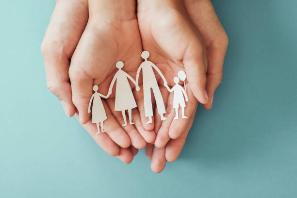 Adult and children hands holding paper family cutout, family home, foster care, homeless charity support concept, family mental health, international day of families Adult and children hands holding paper family cutout, family home, foster care, homeless charity support concept, family mental health, international day of families mental wellbeing stock pictures, royalty-free photos & images
