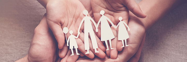 Adult and children hands holding paper family cutout, family home, adoption, foster care, homeless support, family mental health, autism support, domestic violence concept