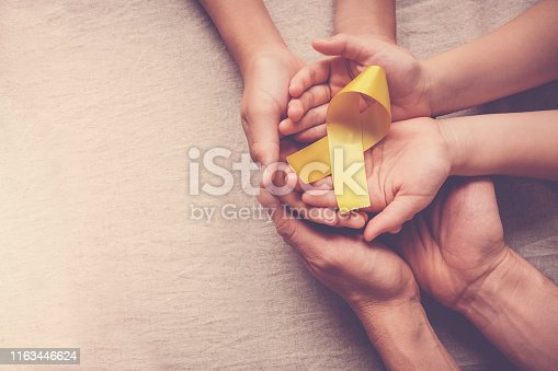istock adult and children hands holding yellow gold ribbon, Sarcoma Awareness, Bone cancer, childhood cancer awareness 1163446624