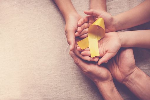 adult and children hands holding yellow gold ribbon, Sarcoma Awareness, Bone cancer, childhood cancer awareness
