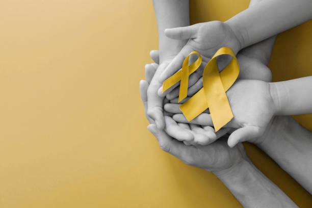 mãos adultas e das crianças que prendem a fita amarela do ouro, consciência do sarcoma, cancro do osso, consciência do cancro da infância - setembro amarelo - fotografias e filmes do acervo